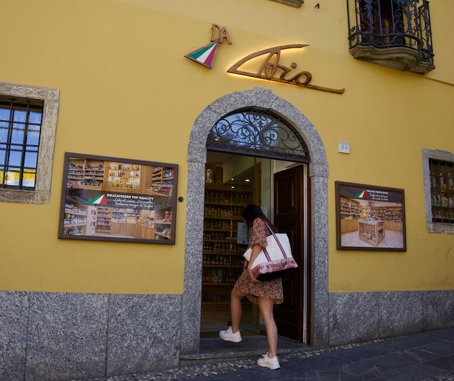 Lady entering the food shop Alimentari da Caio in Bellagio