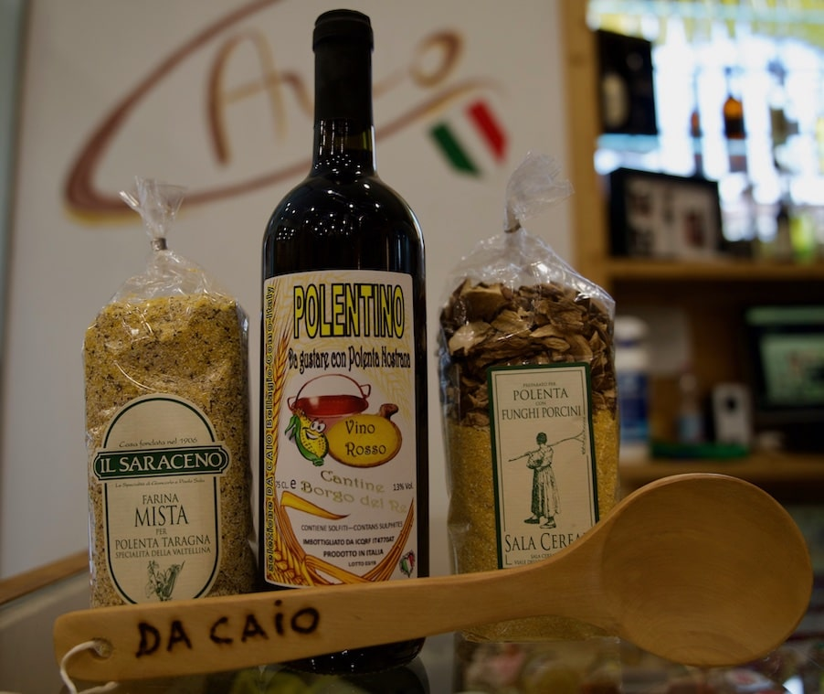 Polenta packages, red wine and a wood spoon